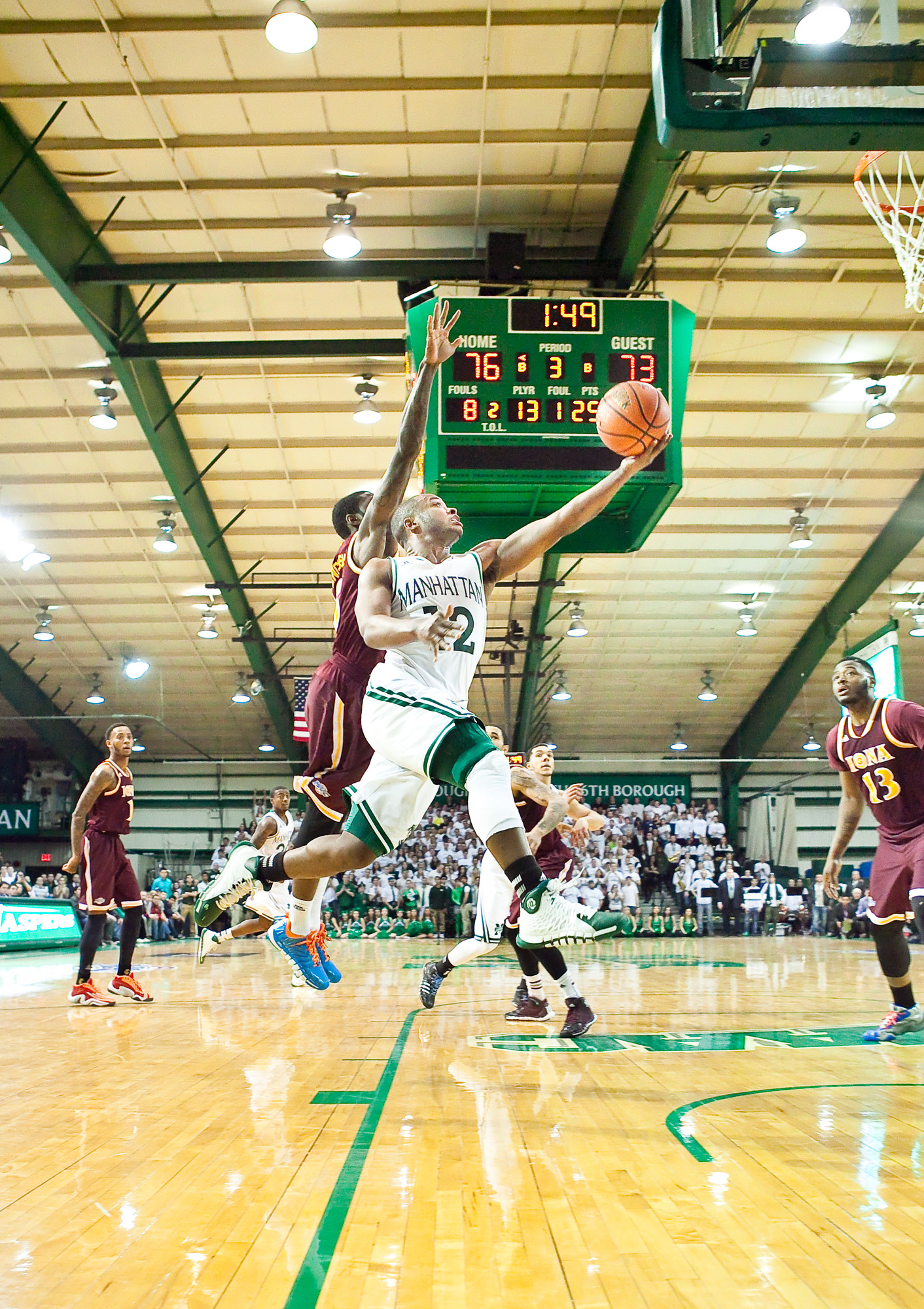 Tyler Wilson, No. 2 for Manhattan College, leaps and scores  over an Iona Gael defender on Saturday at Draddy Gymnasium.