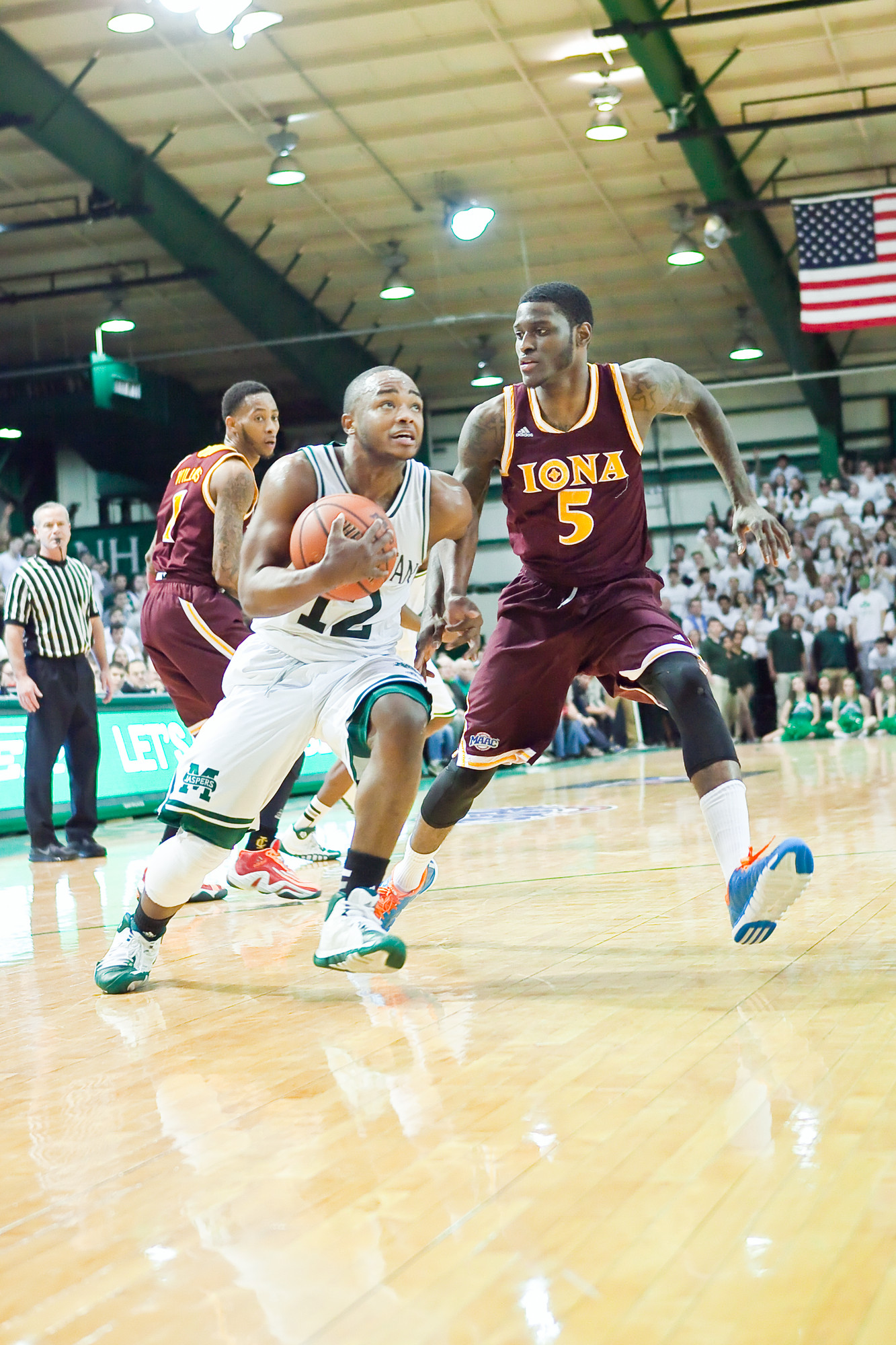 RaShawn Stores, No. 12 for Manhattan College, stays in control of the ball against Iona's A.J. English.