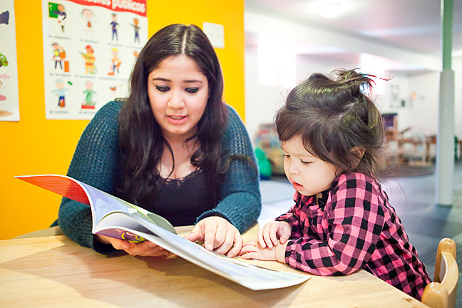 Isabel Martinez reads to a student at her mother's Escuelita on Leibig Avenue.