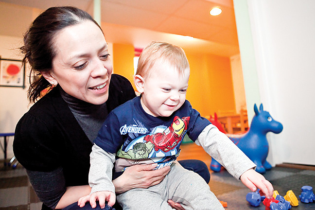 Julisa Martinez, teacher at Escuelita de Sofia spends time with Antonio Geraci as he plays with train blocks on March 13.