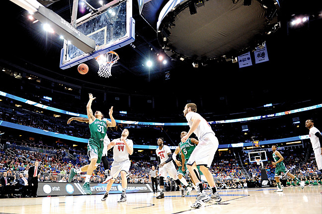 Michael Alvarado, No. 31 for the Manhattan Jaspers, goes strong to the basket against the Louisville Cardinals.