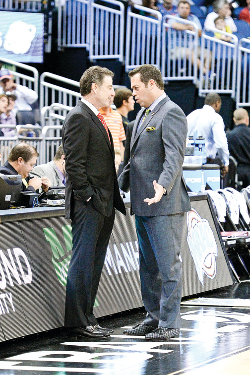 Head Coach Rick Pitino of the Louisville Cardinals (left) enjoys a moment with Steve Masiello of Manhattan College before their NCAA tournament game.
