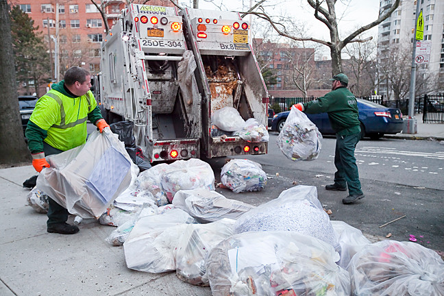 Department of Sanitation workers pick up trash  where rodents are known to visit on west 236th street between Independent Avenue and Hudson Manor Terrace.