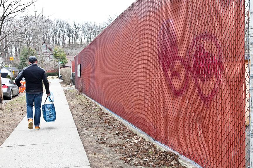 A recently painted over fence exhibits a new tag on West 256th street between Riverdale Avenue and Moshulu Parkway on Monday, April 7.