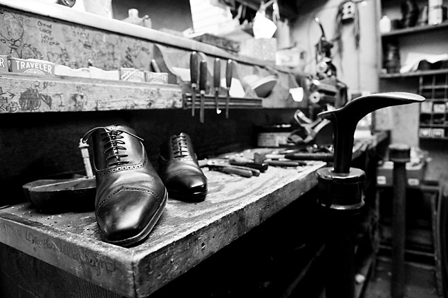 Work counter with a man's dress shoe and a shoe last.
