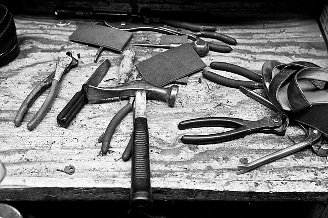 A cobbler's tools including a hammer, clippers and spoon.