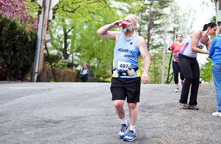 Sy Qruza, 55, grabs a drink on Independence Avenue and West 254th Street on his way to complete the half marathon. He finished at 02:41:49.