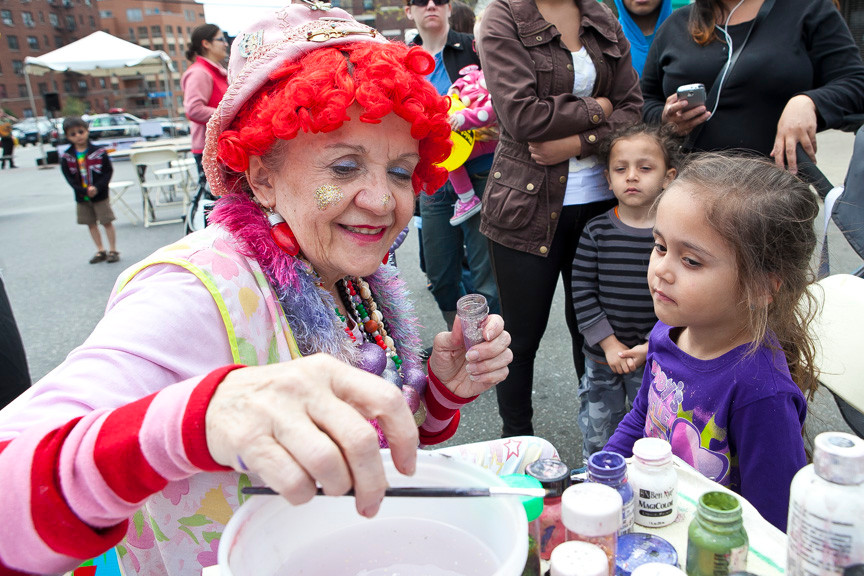 Diamond Oliver, 5, waits as Susan 'Soozy the Clown' McBrian looks for the right brush to paint a lady bug on the child's face.