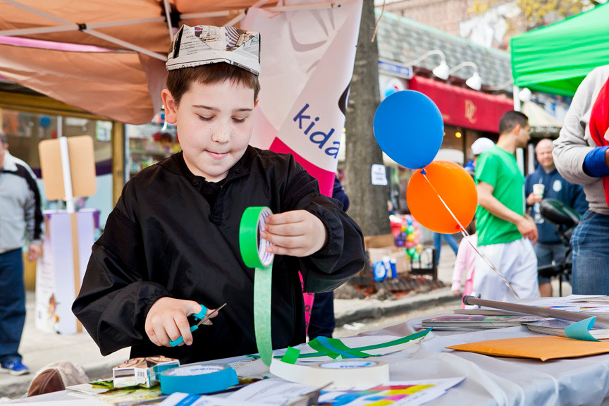 Max Borax, 9, uses tape to make a colorful representation an X for his last letter of his first name at the Kidaroo.