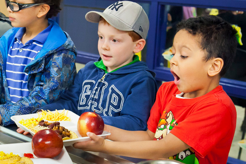 First Graders Caleb Javier, Oliver Heenan and Bronson Branch, right to left, are excited about their choices at the AmPark Neighborhood School cafeteria line.