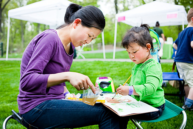 Ying Hung watches her daughter Ellie Lee, 3, paint her surroundings with watercolor paint and supplies provide by The New York Botanical Gardens as part of the Mother's Day Weekend Garden Party on Saturday.
