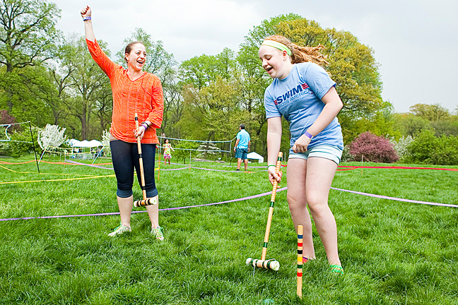 Andria O'Brian, 43, praises her daughter Meghan O'Brian, 12, as she completes a game of crocket on Daffodil Hill at The New York Botanical Gardens as part of the Mother's Day Weekend Garden Party on Saturday.