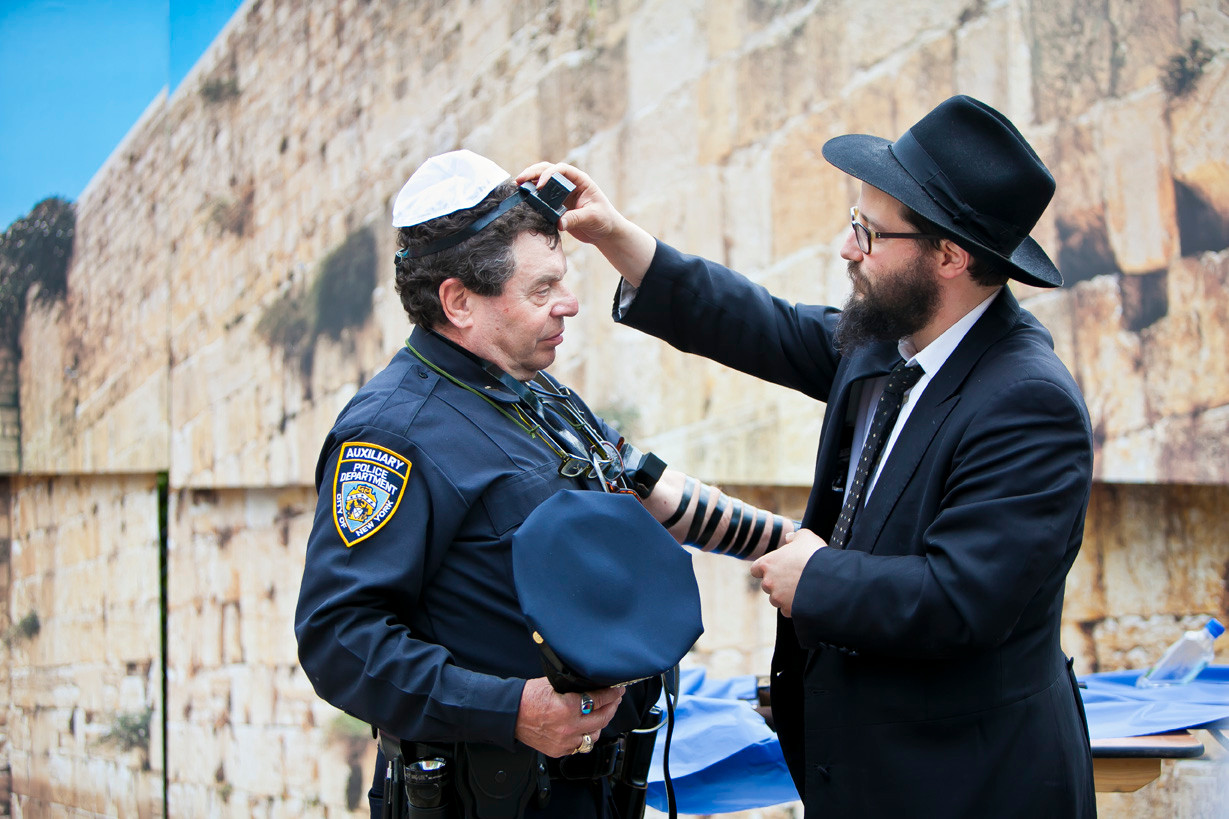 Peter Heller, an auxiliary police officer with the 50th Precinct, goes through a Tfillin ceremony during Chabad Lubavitch of Riverdale's Lag B'Omer celebration on Sunday.