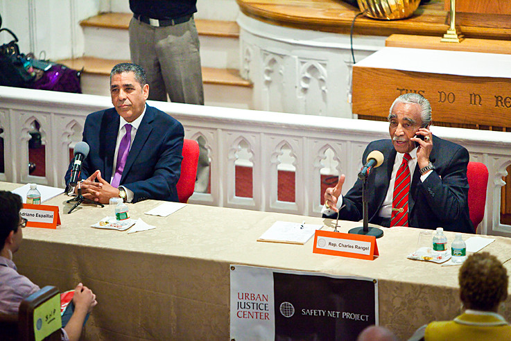REP. CHARLES RANGEL, right, in the middle of the fake phone call during his debate against state Sen. Adriano Espaillat, left, and Rev. Michael Walrond (not pictured).