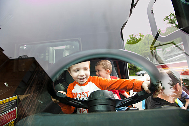 Jonah Goldberg, 3, and Isaiah Yolkut, 4, take the driver's seat (without the keys) of a garbage truck at Riverdale Temple Nursery School on May 21.