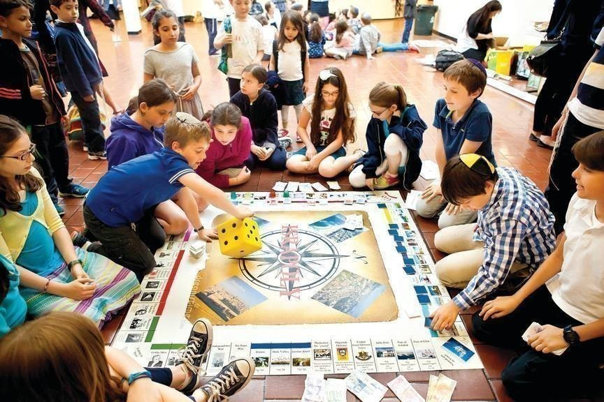 Children from Salanter Akiba Riverdale Academy learn about Israel by playing board games like 'Israpoly' on May 28.