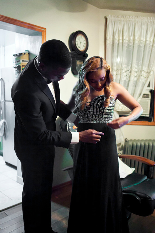 Andrew Morris, 21, helps Destiny Burgos, 17, with last minute fixing of her dress at her home. They will be attending the final prom for John F. Kennedy High School.