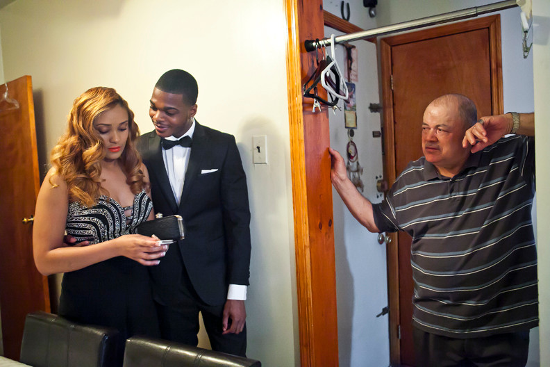 Jesus Burgos looks on as his daughter Destiny, 17, and her boyfriend Andrew Morris, 21, prepare at her home for the dance.