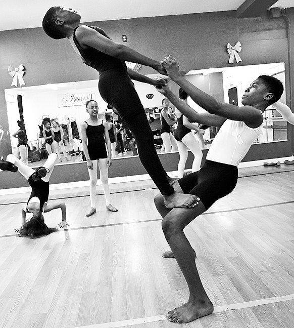 Babou Sanneh, 13, performs a balancing feat with Jaquan Morgan, 14.