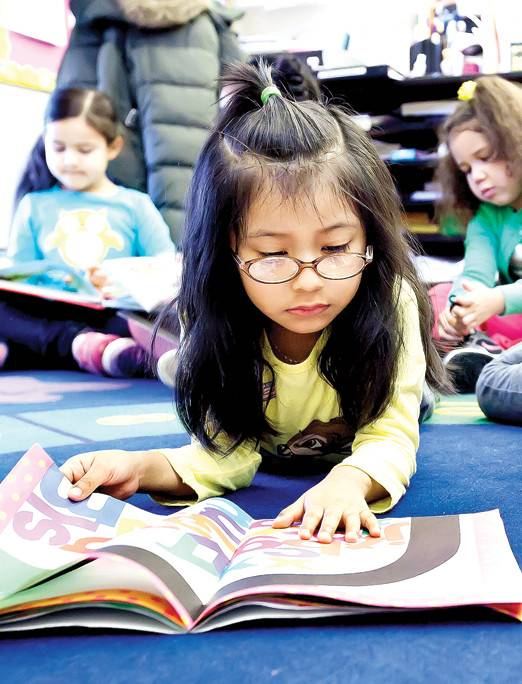 Angelyn Dominguez, is engrossed in a book at the Kingsbridge Heights Community Center. The organization is expanding its pre-K offerings for the fall.