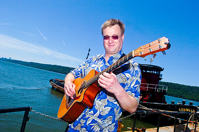 Steve Oates, one of dozens of musicians on two stages, plays the song 'Classical Gas' on the dock at RiverFest.