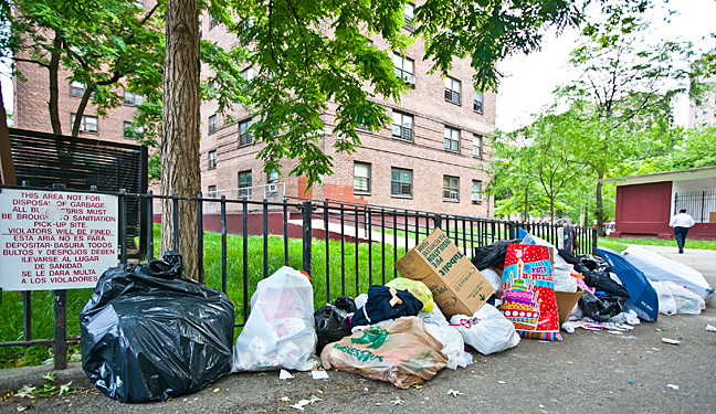 Trash piles up outside the Marble Hill Houses, where residents say garbage presents a chronic problem.