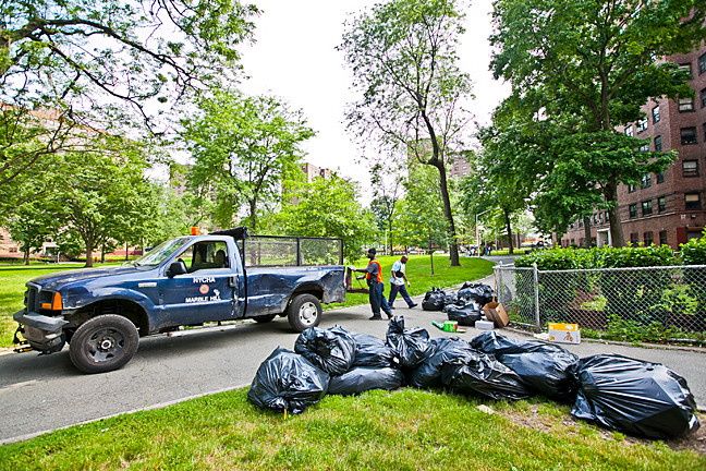 NYCHA workers remove several pounds of trash bags near 5360 Broadway on Monday in a NYCHA complex.