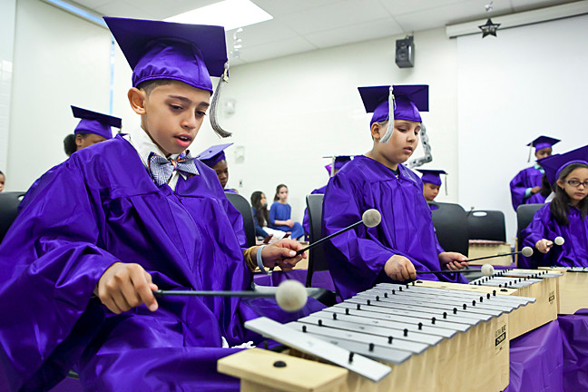 Angel Valdez, 10, Anthony Salaman, 11, and the rest of the AmPark Neighborhood School fifth grade graduating class perform on June 19.