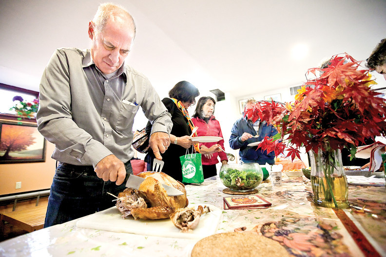 John Benfatti, who organizes an overnight shelter for homeless men at the Riverdale-Yonkers Society for Ethical Culture, carves a turkey for a pre-Thanksgiving gathering at the Riverdale Yonkers Society for Ethical Culture Society last year. Photo by Marsil Diaz/The Riverdale Press