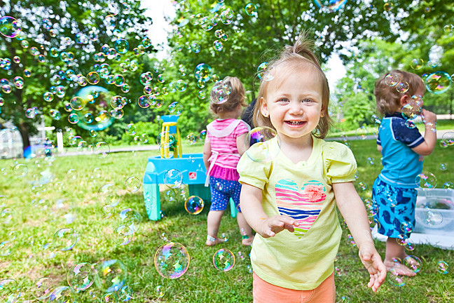 Ali's Art in the Park in Seton Park on Tuesday, 17, 2014, 16-month-old Julie Remin is delighted to find herself surrounded by bubbles. The class began this month and runs through August, working with early learners to help them develop their motor and social skills.