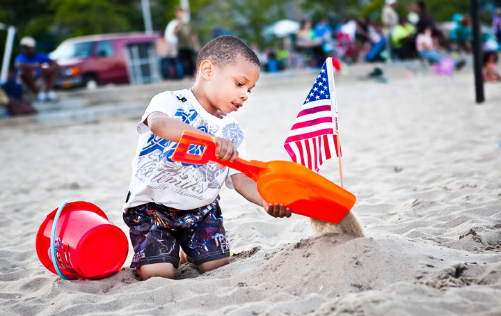 Emmanuel Adon, 5, plants an American Flag at Orchard Beach prior to the Bronx's annual Independence Day fireworks display.