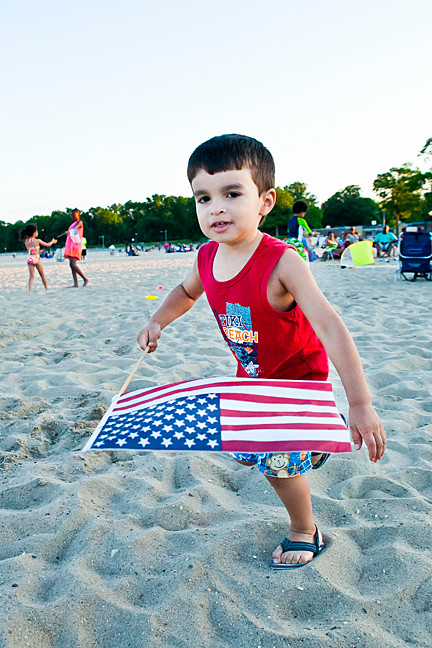 Geovanne Moreno, 3, runs in the sand waiving the American Flag on June 27 at Orchard Beach prior to the annual fireworks.