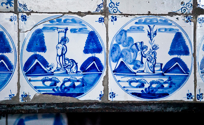 Delft tile surrounds the fireplace in the west parlor.