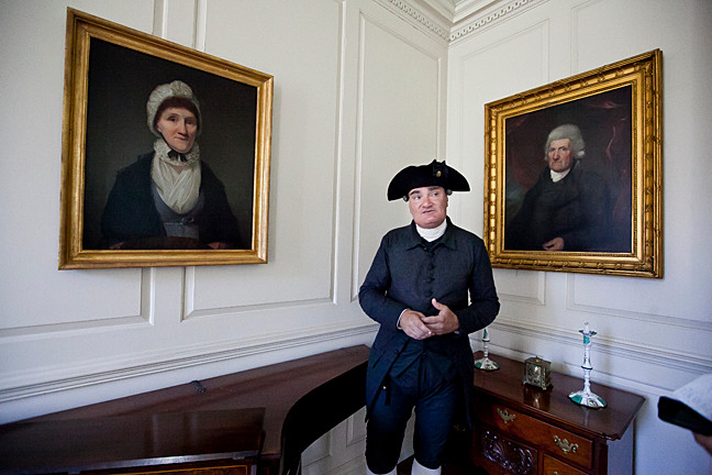 Michael Grillo, 52, a museum educator, stands between portraits of Eve Van Cortlandt and Augustus Van Cortlandt in the east parlor room.