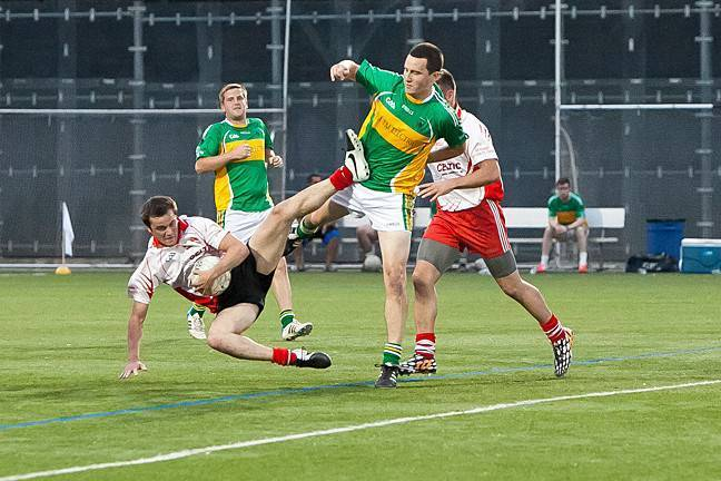 Thomas Wyle, of Tyrone, goes down with the ball as Niall Croke, playing for St. Barnabas, stands nearby at Gaelic Park on July 10.