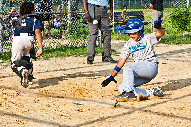 Rafael Reyes slides to score for the Yankees (his jersey notwithstanding) against the Mariners in the Kingsbridge Little League championship at Van Cortlandt Park on July 8.