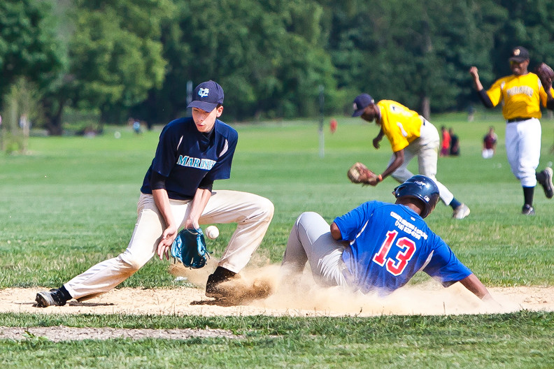 Esteban Perez  for the Van Cortlandt baseball league Blue Jays slides in safely as Josue Corona for the Mariners tries to handle a late and tough throw  at Van Cortlandt Park on July 18.