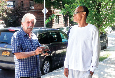 Riverdale resident Rene Rodriguez, 73, prepares to give a con artist who goes by the name Tony a wad of cash on July 18 at the corner of Johnson Avenue and West 230th Street.