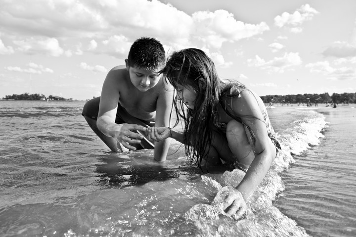 Kevin Rodriguez, 12, and Gabby Rodriguez, 8, look for rocks and other objects among the gentle waves.