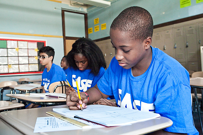 Sajon Rattigan, 13, Anita Oduro, 14 and Ifthehar Ahmed, 14, work on graphing points to a coordinate plane in a summer geometry class that is part of Sports and Arts in Schools at DeWitt Clinton High School.