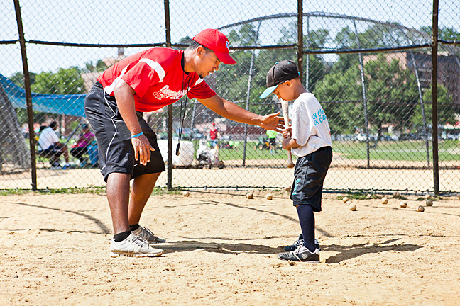 Johnathan Rosario, 21, coaches proper batting technique to Jadiel Vasquez, 6, at the Van Cortlandt League morning baseball camp on Wednesday, July 30, 2014.