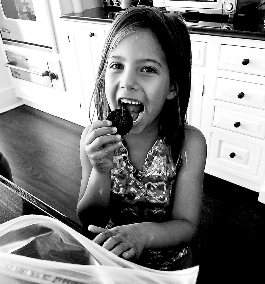 Maya Moriles, 6, takes a bite from an Oreo cookie before working on the recipe.