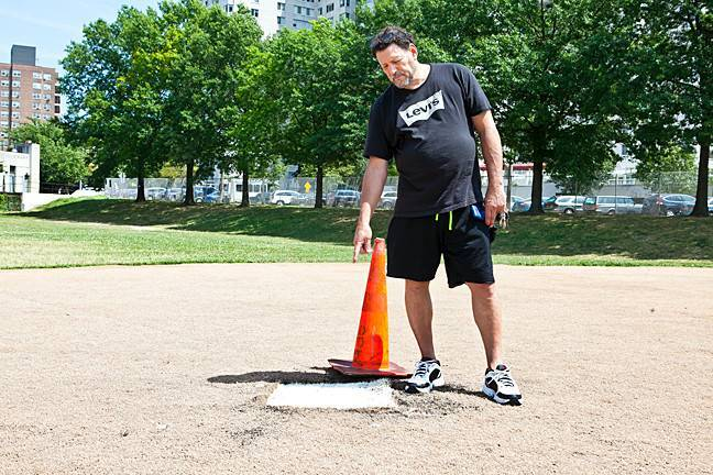 Joe Brender, 61, points to where the swastika was burned into between first and second base on the ball field of Seton Park in the early hours of Sunday morning.