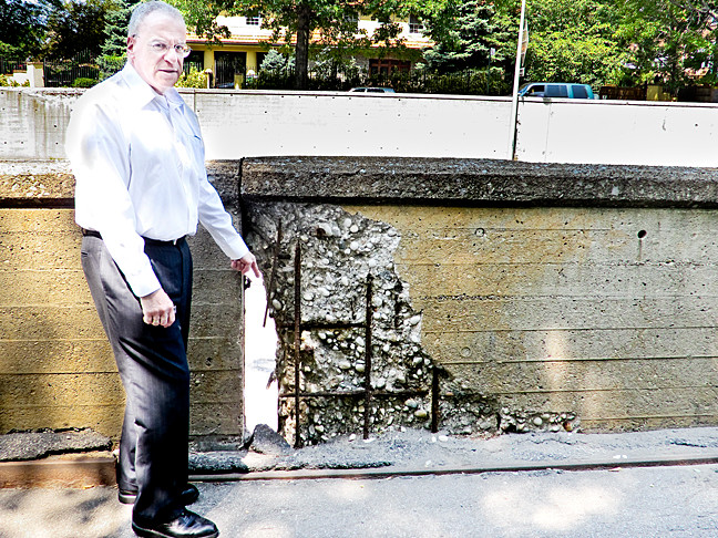 Assemblyman Jeffrey Dinowitz points to a dangerously deteriorated retaining wall along the Henry Hudson Parkway between West 231st and West 235th Streets. The legislator has called on the city's Department of Transportation to make immediate repairs.