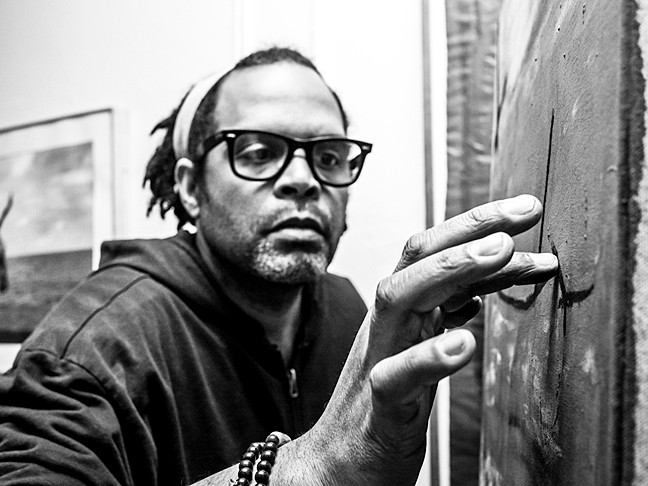 Artist Alexis Mendoza fine tunes a charcoal etching, photographed by Osjua A. Newton.