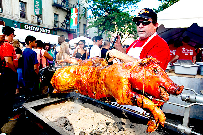 John Pikolas, 45, photo, checks on the pig that cooked from 7 a.m. to 5:30p.m. at the festival.
