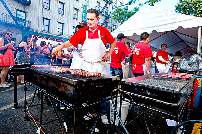 Peter Servedio, 68, Owner of Peter's Meat Market checks on the sweet sausage at the Ferragosto 2014 street festival on Arthur Avenue on Sunday.