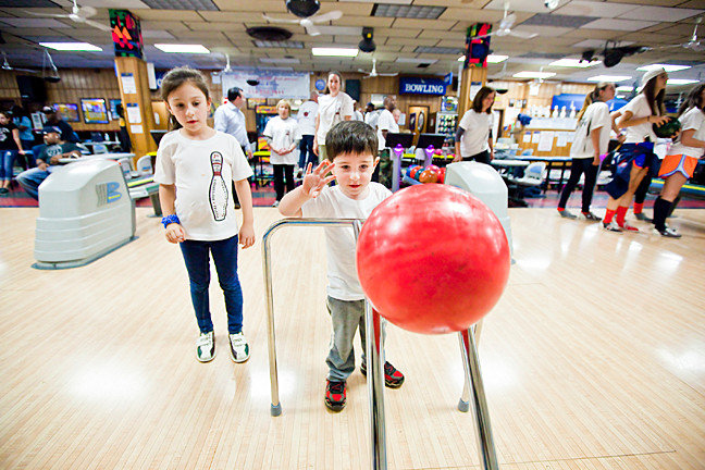 Anna Blanco, 7, watches her brother Alex, 3, take a turn at Bowlerland.