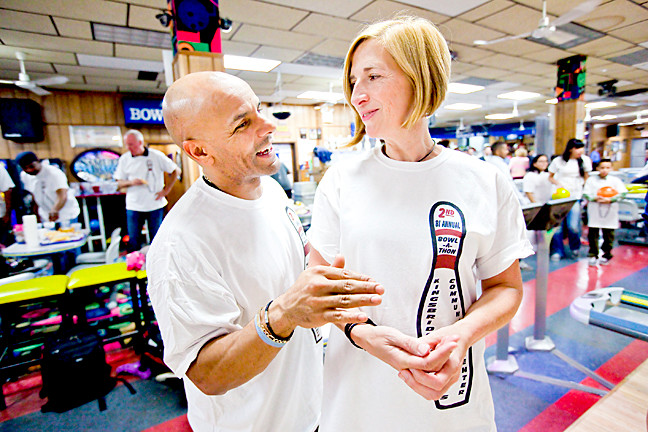 David Corona, 46, gives bowling tips to Board Member Lisa Lindvall, 51.