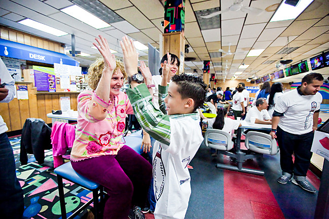 Lori Spector, 70, Deputy Director of Kingsbridge Heights Community Center congratulates Jacob Colón, 10, after his turn at bowling.